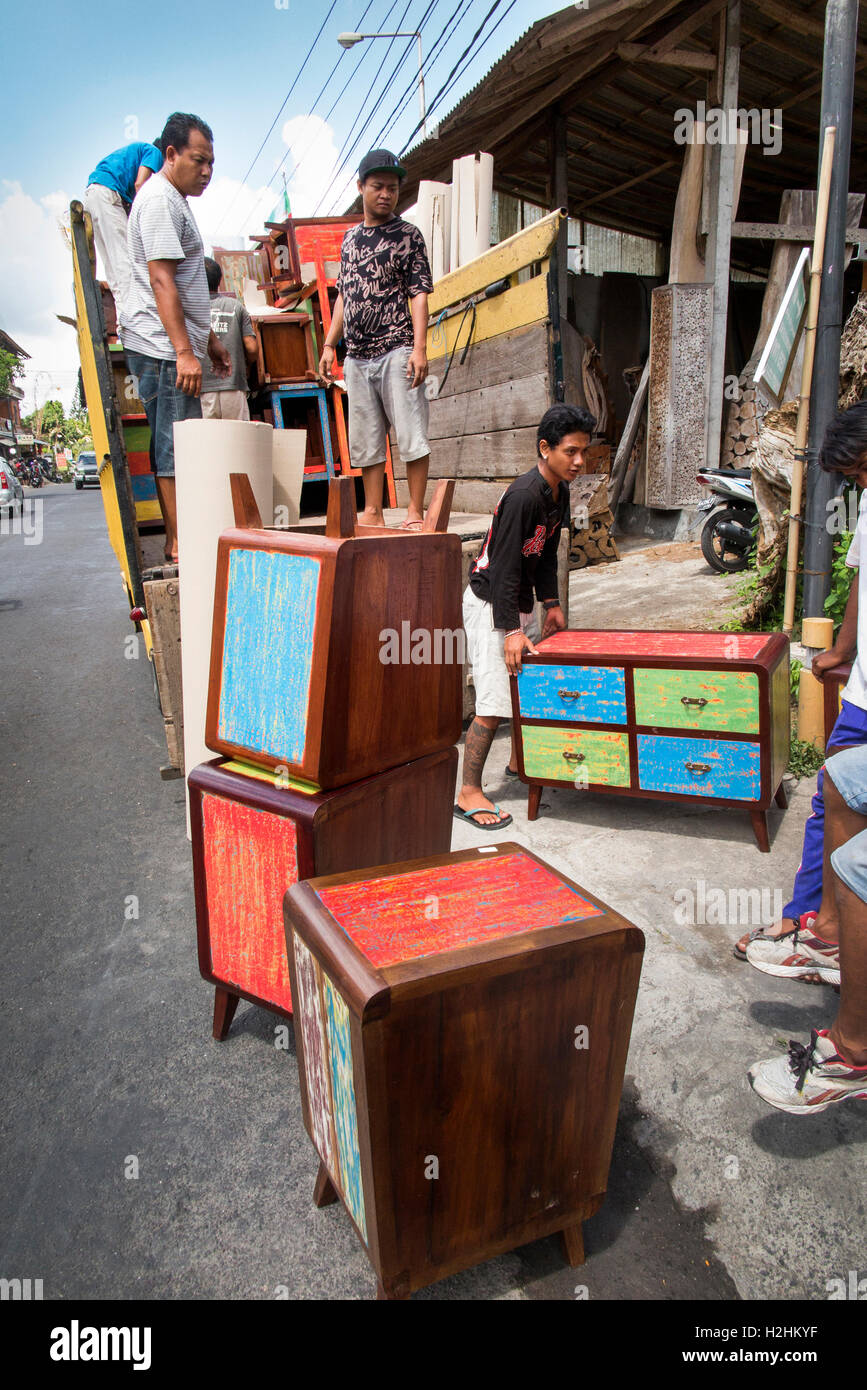 Indonesia, Bali, Mas, men loading lorry with reproduction newly made shabby chic painted furniture - Stock Image