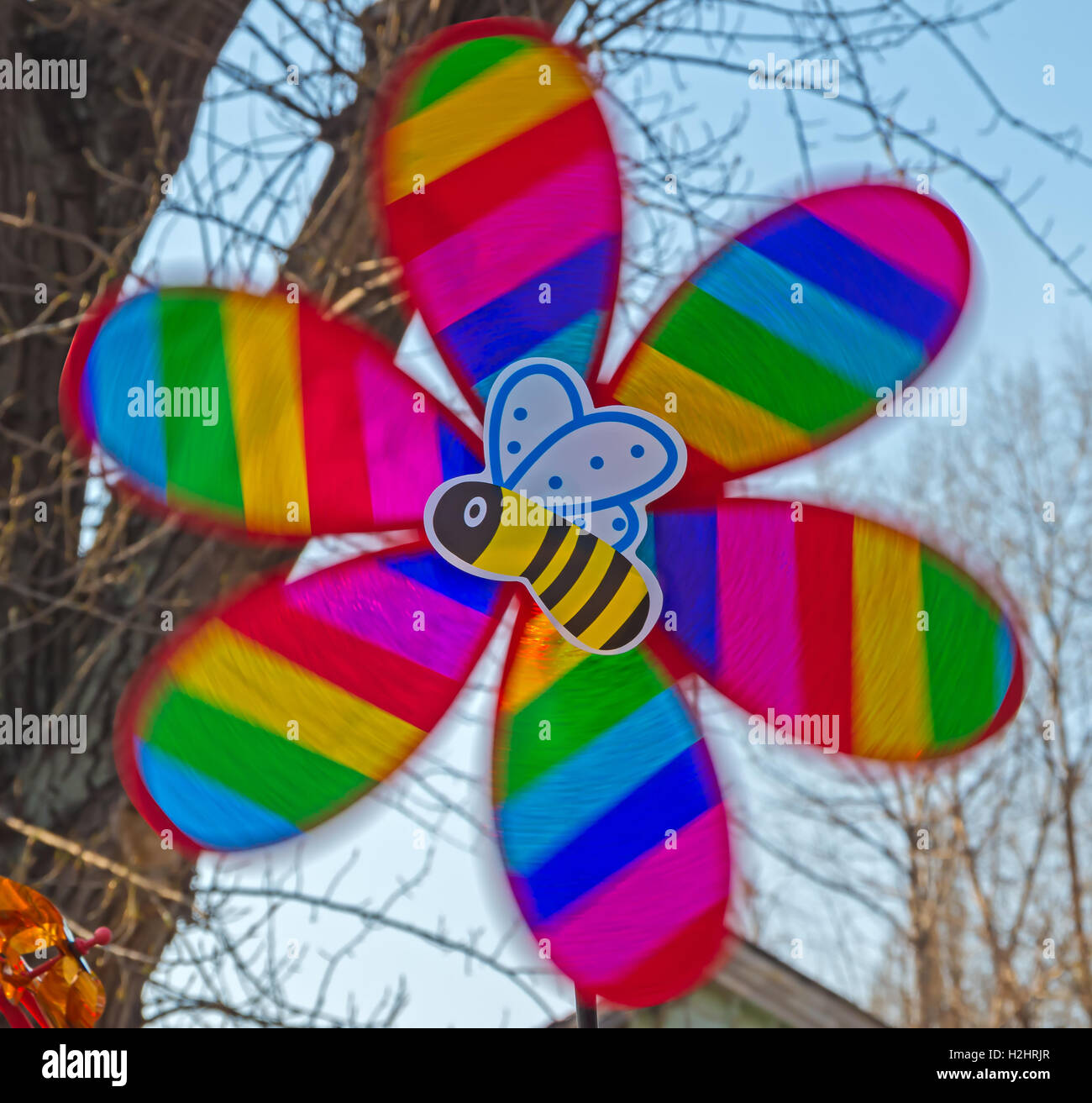 Children's multi-colored toy in the form of a propeller and bee in motion - Stock Image