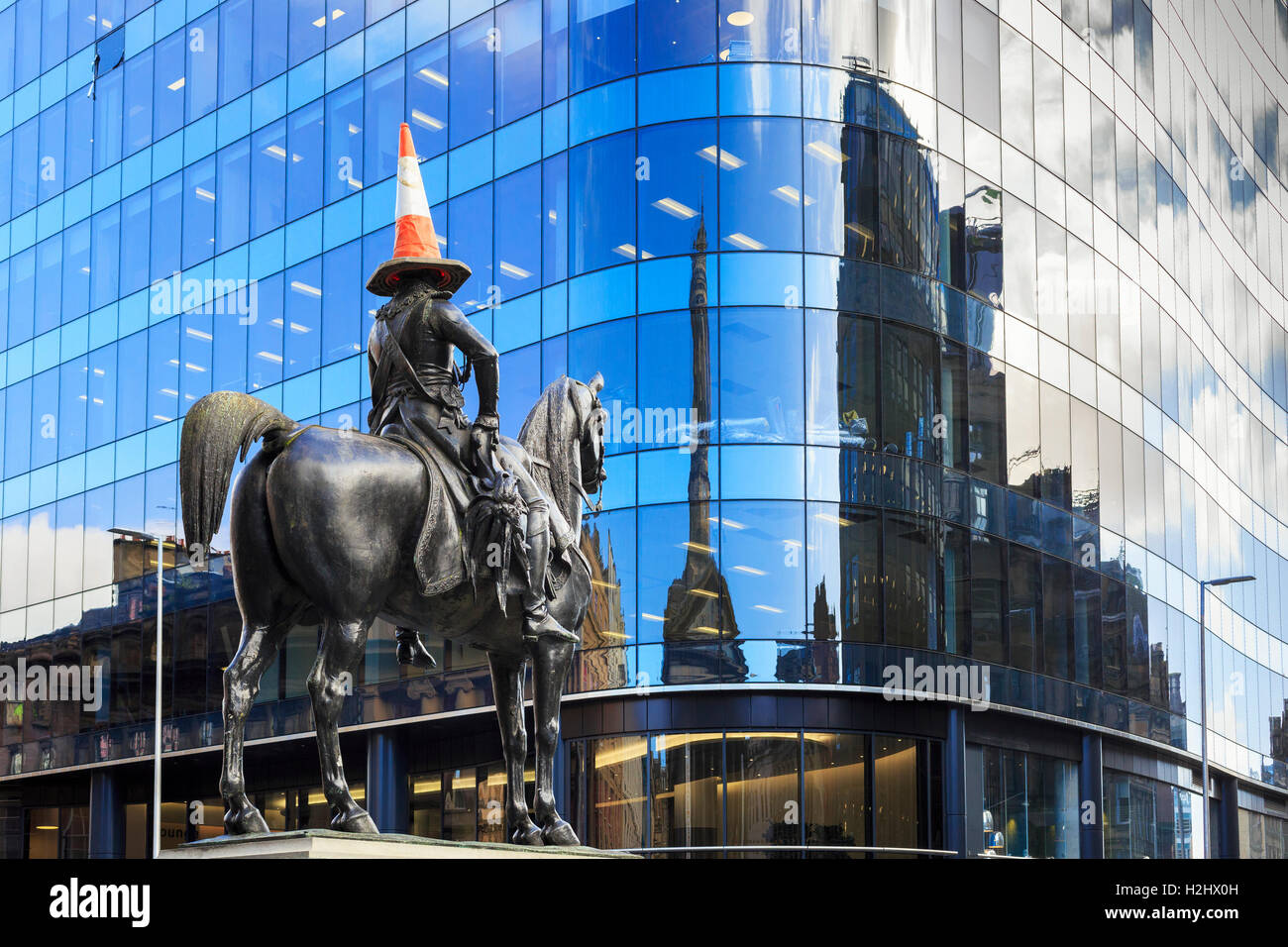 Duke of Wellington statue in Royal Exchange Square, Glasgow, Scotland with the iconic traffic cone on its head against - Stock Image