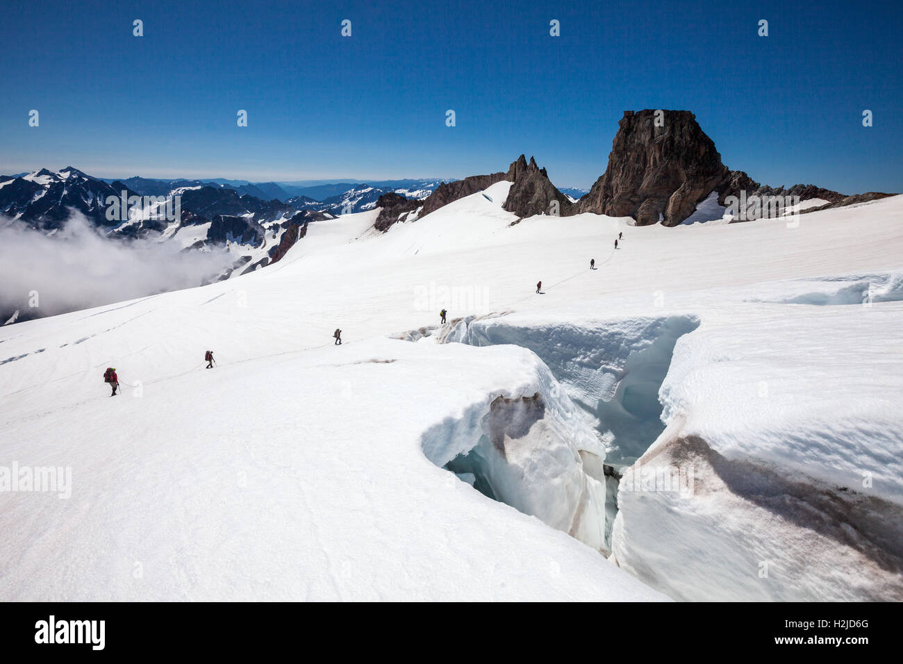 Two rope-teams of mountaineers crossing a crevasse on Glacier Peak in the North Cascades Mountains, Washington State, - Stock Image