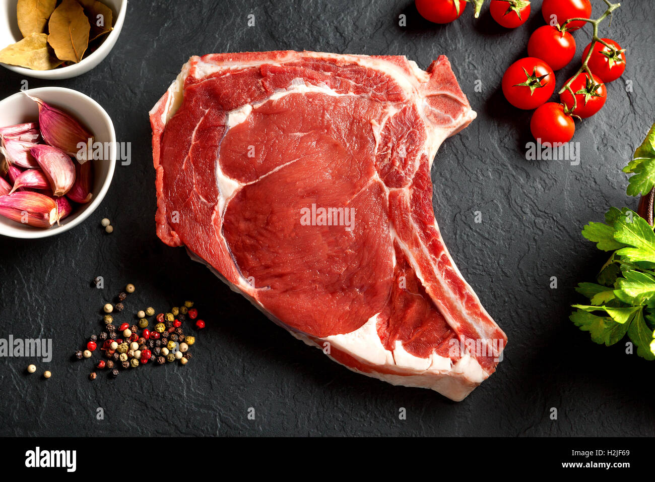Still life raw thick rib over black background from above - Stock Image