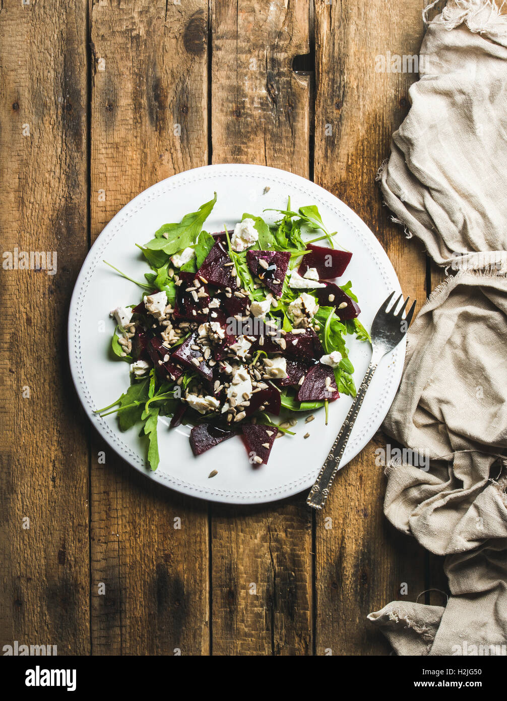 Arugula, beetroot, feta cheese and sunflower seed salad in plate - Stock Image