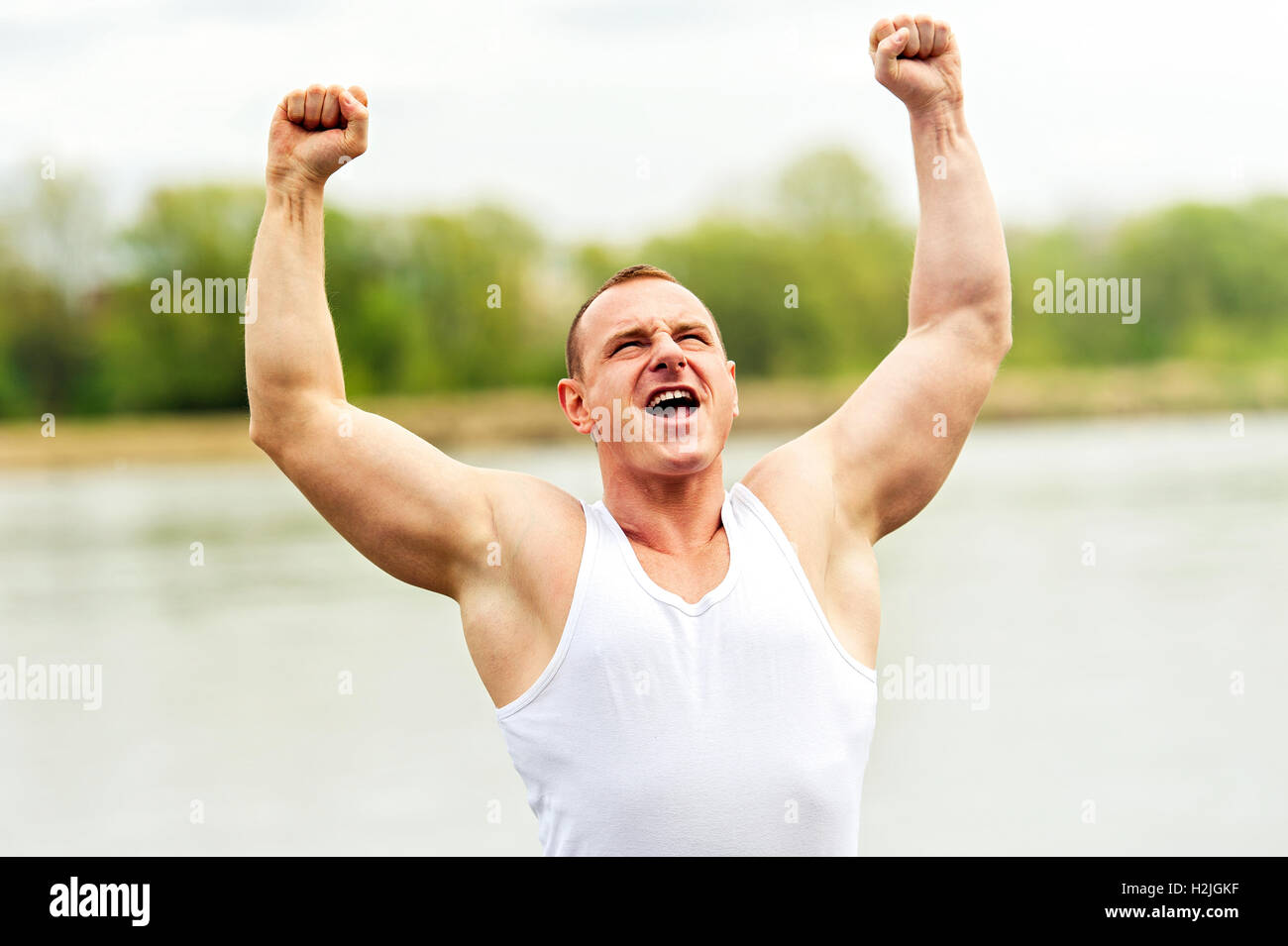 Active man with arms up wining. Shout. - Stock Image