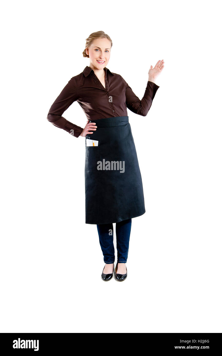 Waitress pointing. Woman in apron smiling happy isolated on white background. - Stock Image