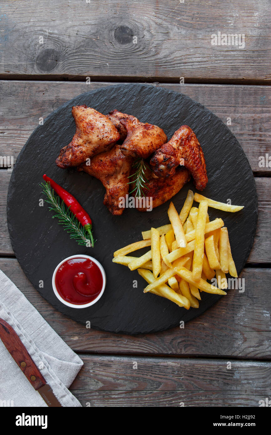 Fried roasted chicken wings french fries and sauce - Stock Image