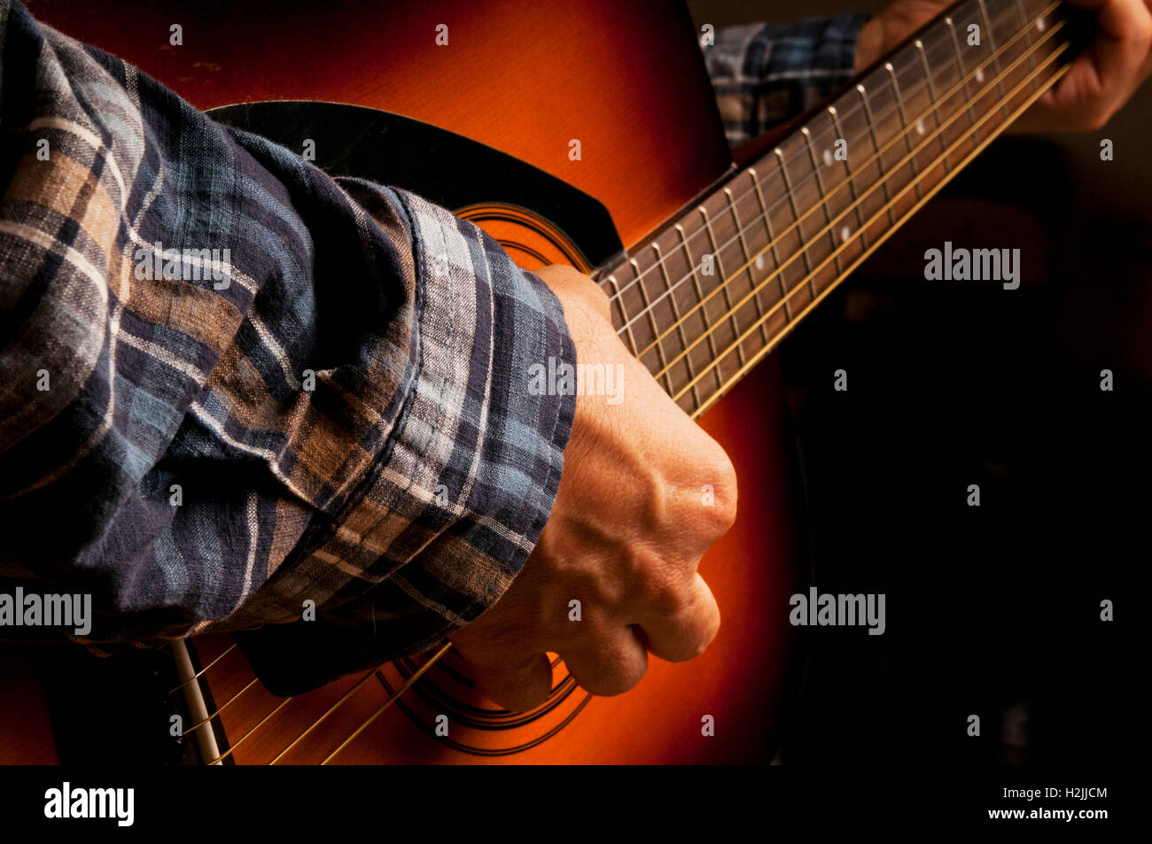 male guitarist playing an acoustic guitar - Stock Image