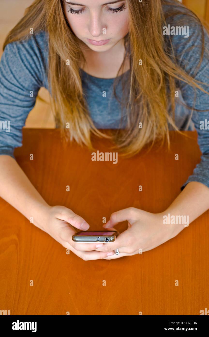 brunette tween girl texting - Stock Image