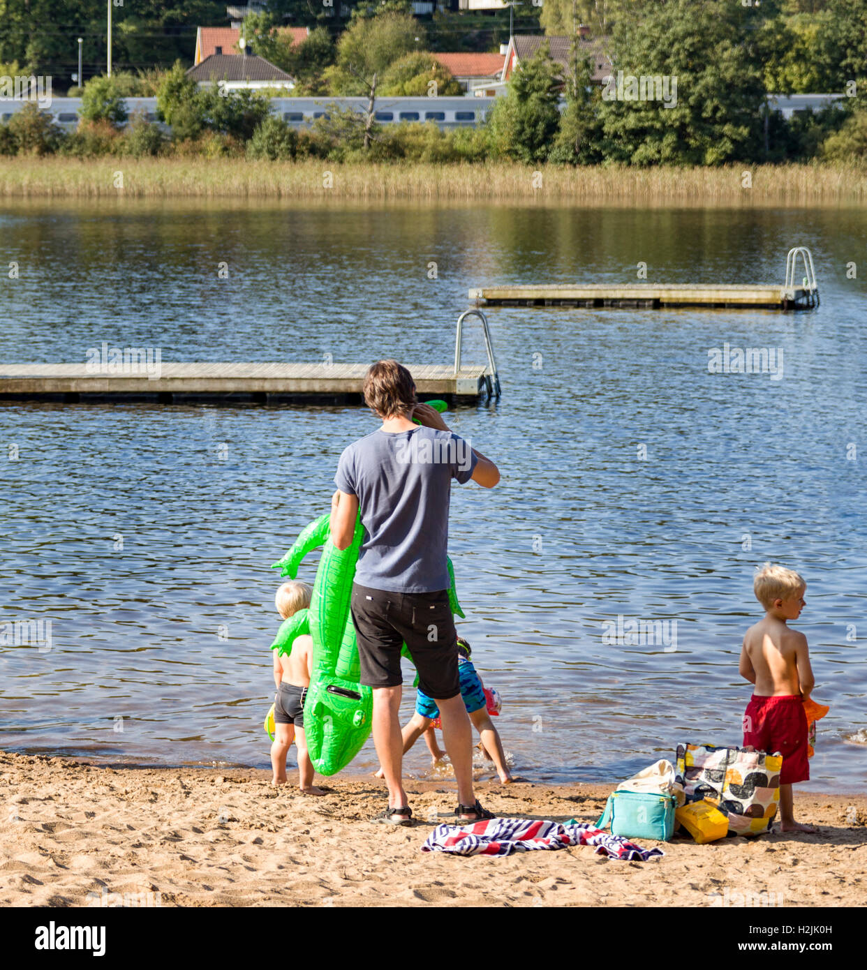 Family father with inflatable crocodile and children at the beach  Model Release: No.  Property Release: No. - Stock Image