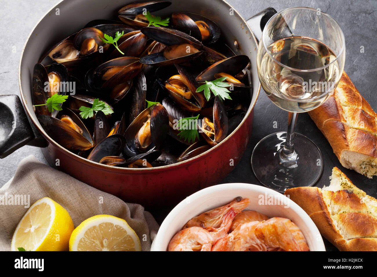 Mussels, shrimps and white wine on stone table - Stock Image