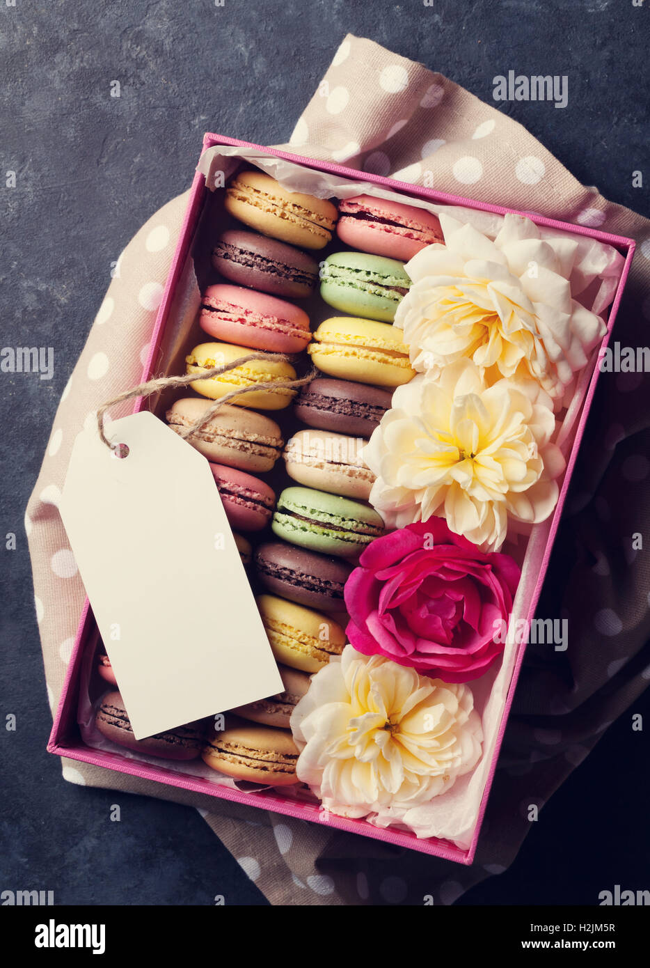 Colorful macaroons and flowers on stone table. Sweet macarons in gift box. Top view. Toned - Stock Image