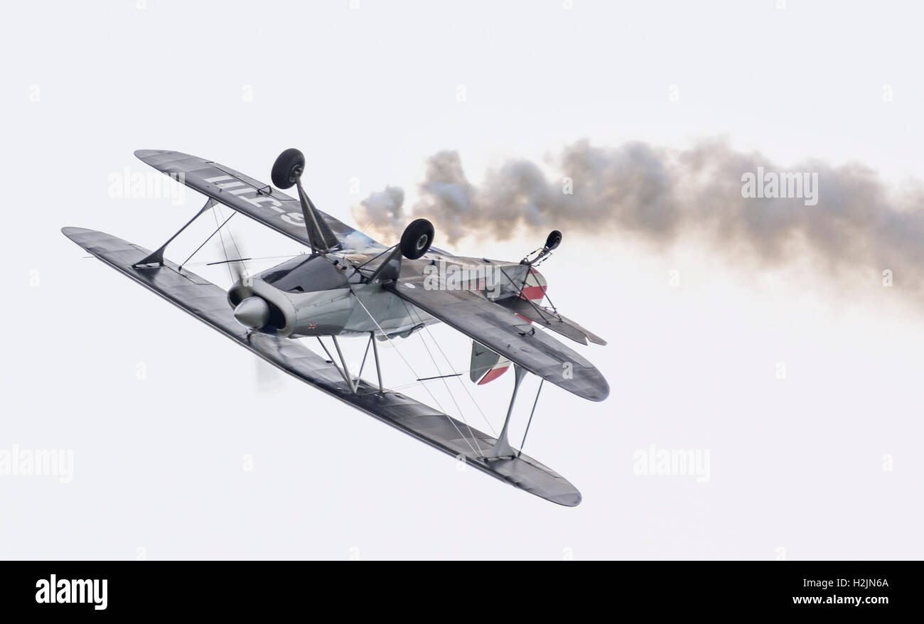 Biplane upside down practicing for an air display. Aircraft is G-J111 single seater single propeller biplane. - Stock Image