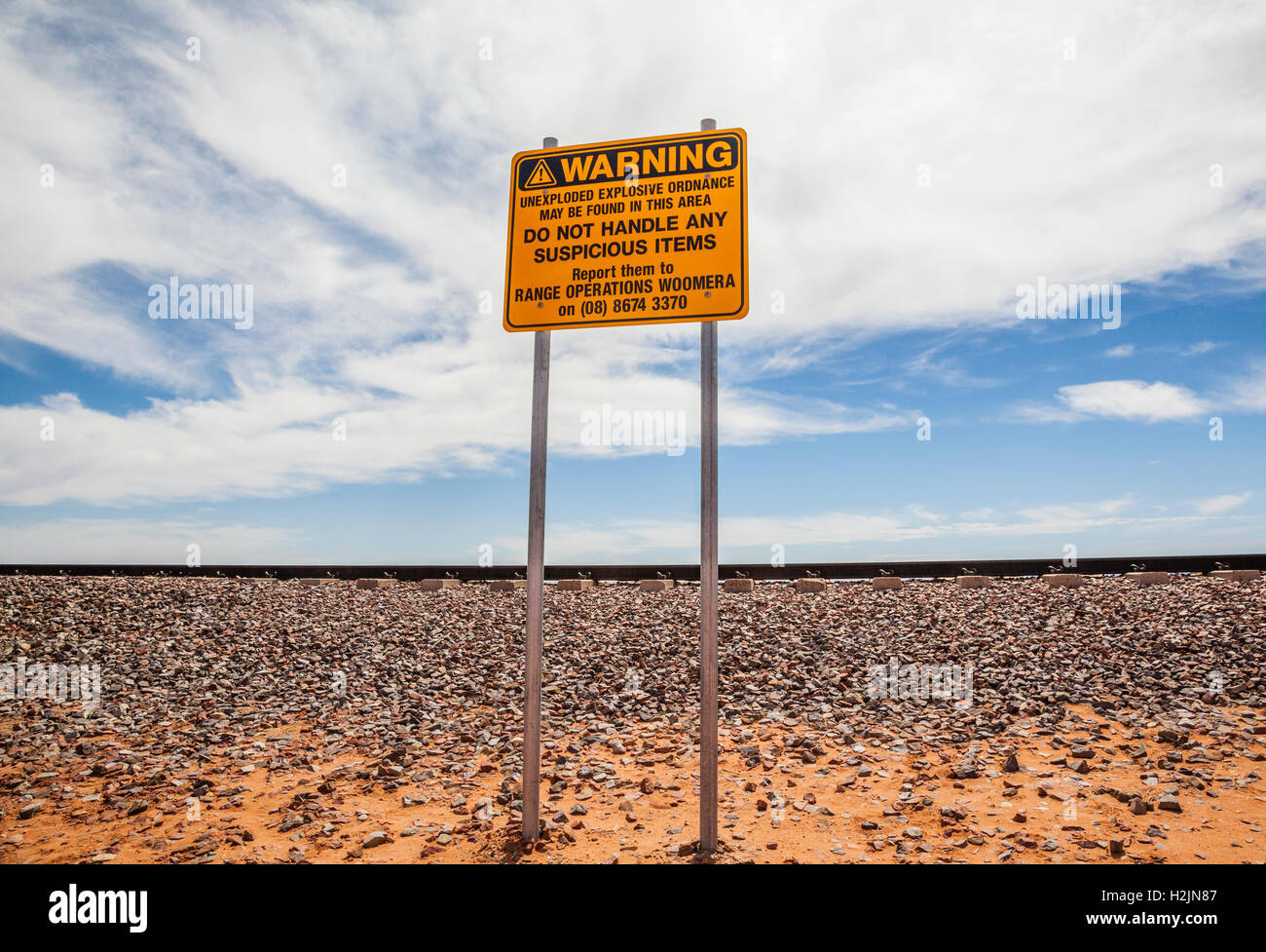 ordnance warning sign at railway track of the New Ghan at Lake Hart near the Stuart Highway, South Australia - Stock Image