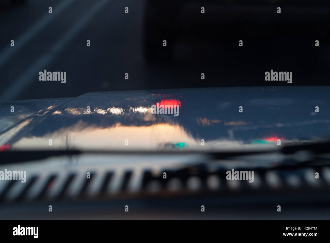 Evening reflection off of poorly painted automobile hood. - Stock Image