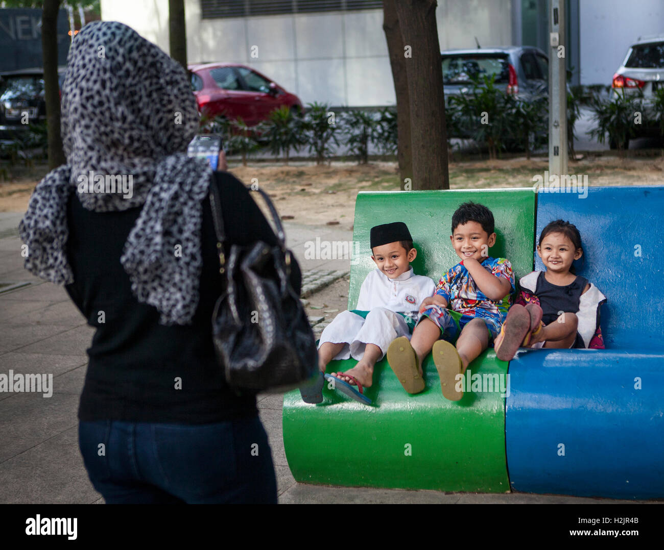 Happy Muslim children sit on a park bench while their mother takes their picture in Kuala Lumpur, Malaysia. - Stock Image