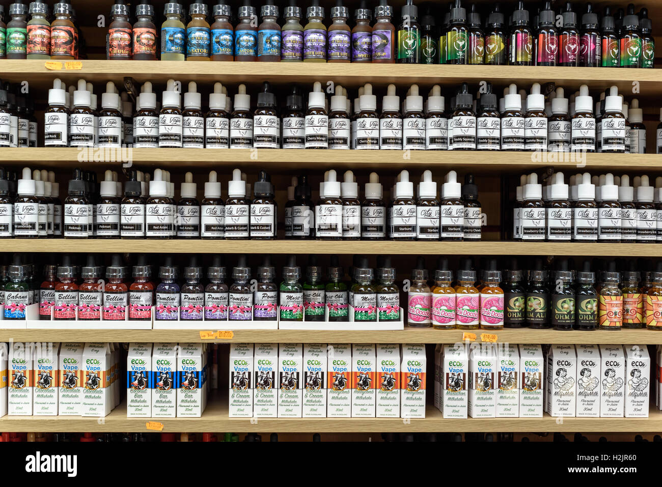 Rows of bottles of liquids of different flavors for vaping and vapors on display in a shop - Stock Image