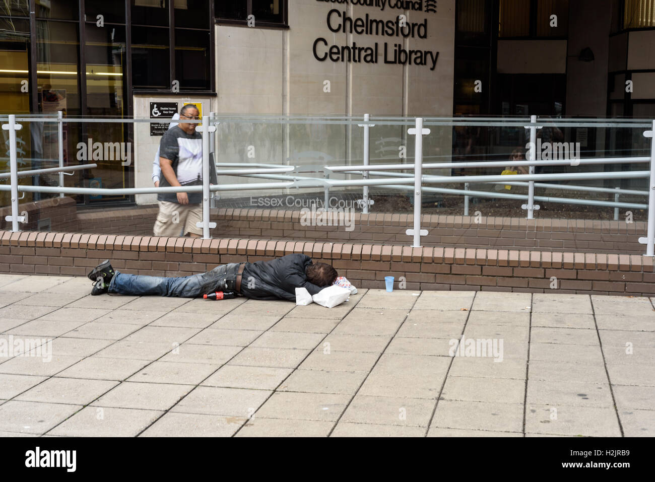 Sleeping homeless man sleeps outside Chelmsford County Council Library in the summer of 2016 in Essex England - Stock Image