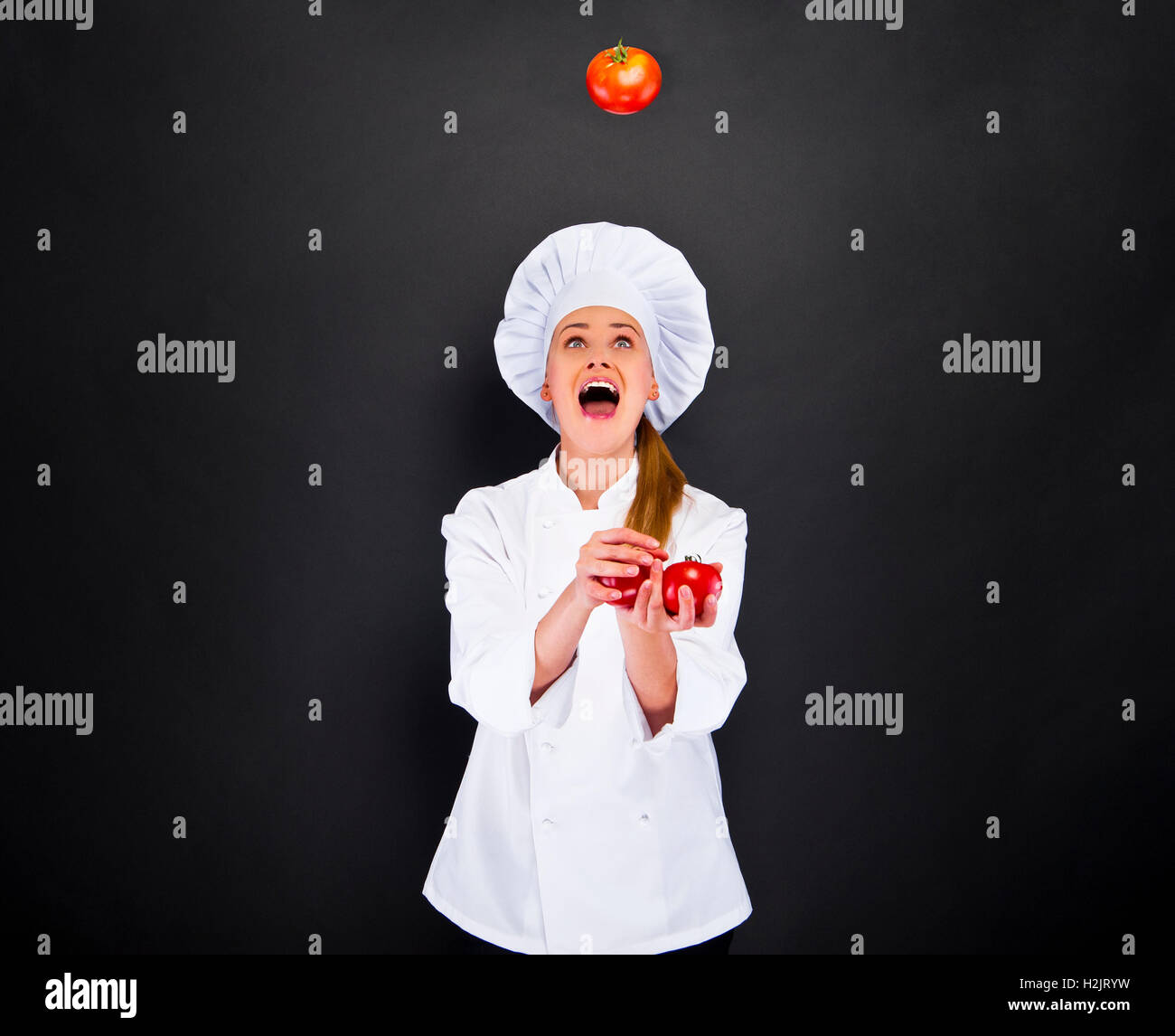 Portrait of young woman chef with tomatos juggle - Stock Image