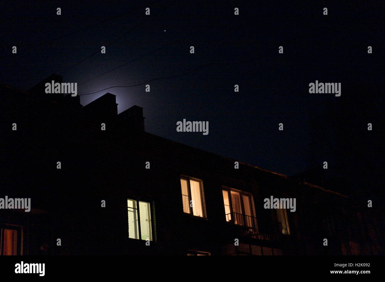 Moon glow over a rooftop of a house at night - Stock Image