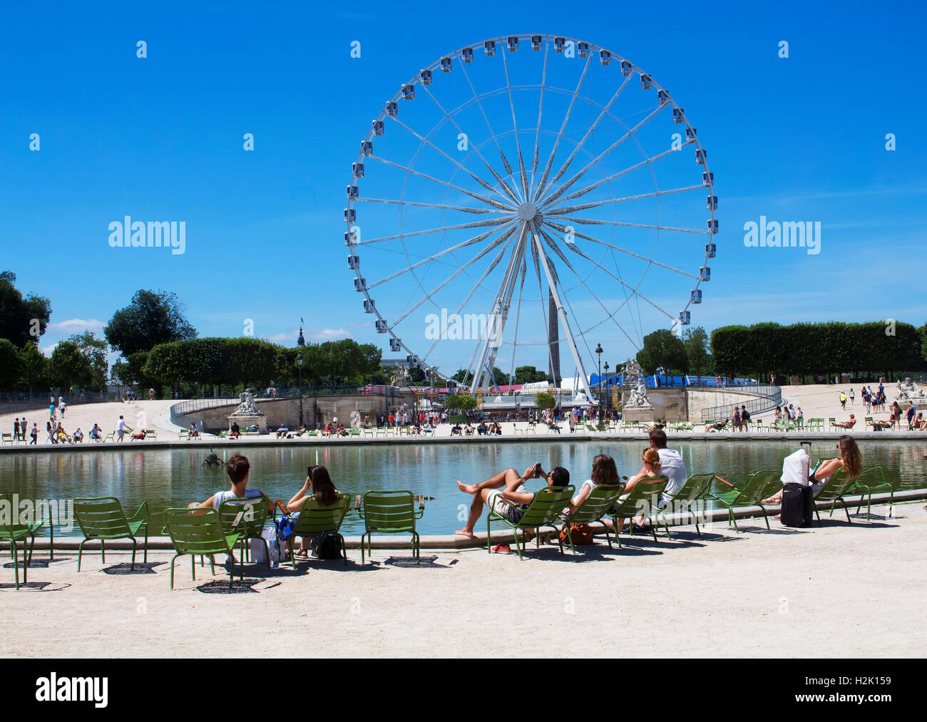 People Hang Out By Pool In Front Of Ferris Wheel At Jardin Des Stock