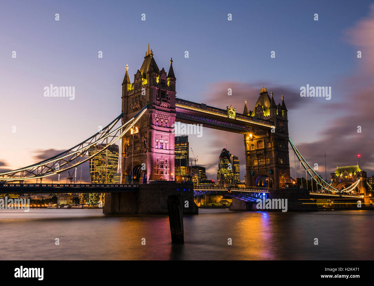 Lights and boats captured at dusk in a long exposure of Tower Bridge, London, UK - Stock Image