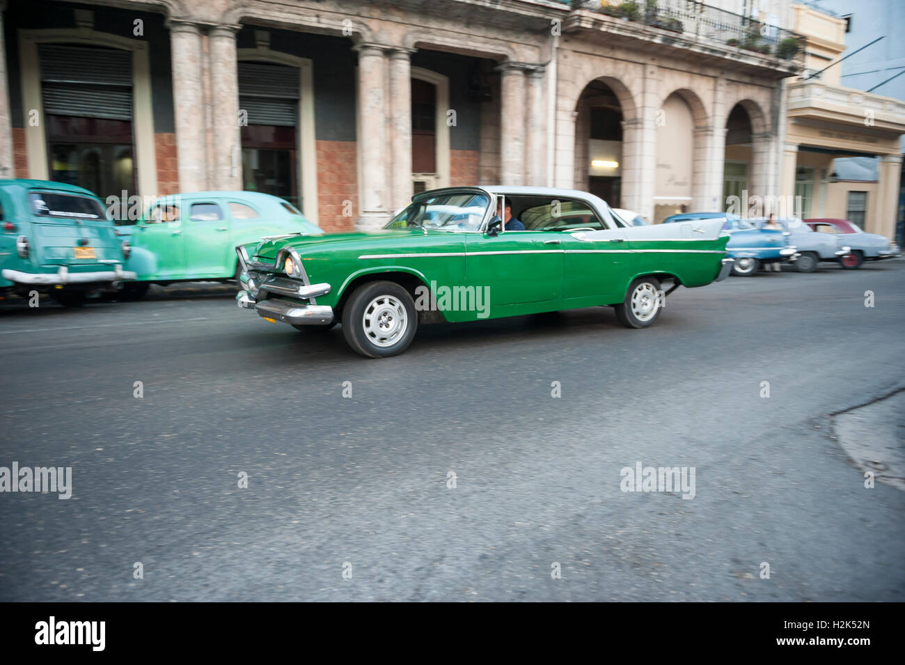 HAVANA - JUNE 15, 2011: Old American car drives in front of the traditional architecture of a colonial arcade. - Stock Image