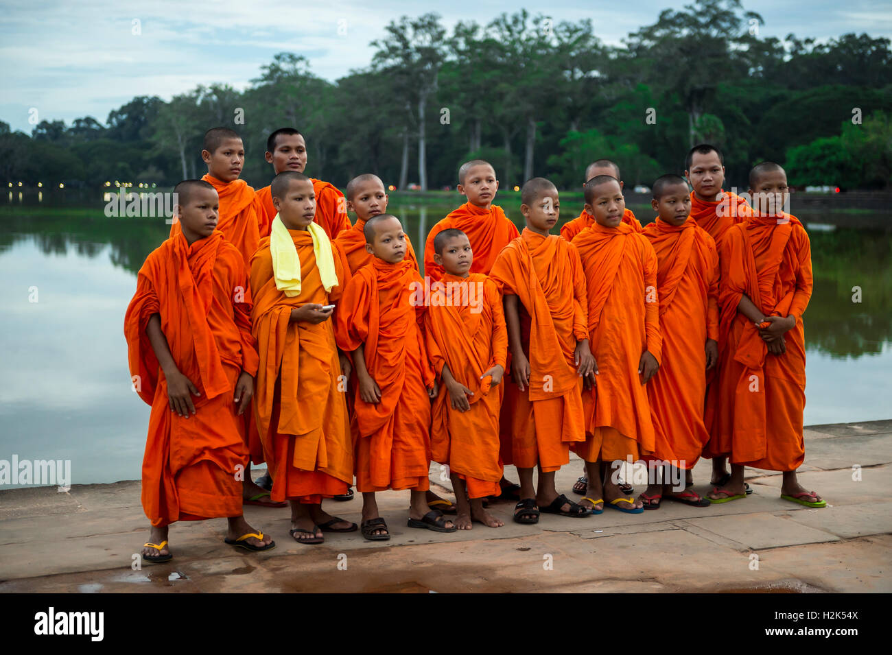 SIEM REAP, CAMBODIA - OCTOBER 30, 2014: A group of novice Buddhist monks in orange robes pose on the moat to Angkor - Stock Image