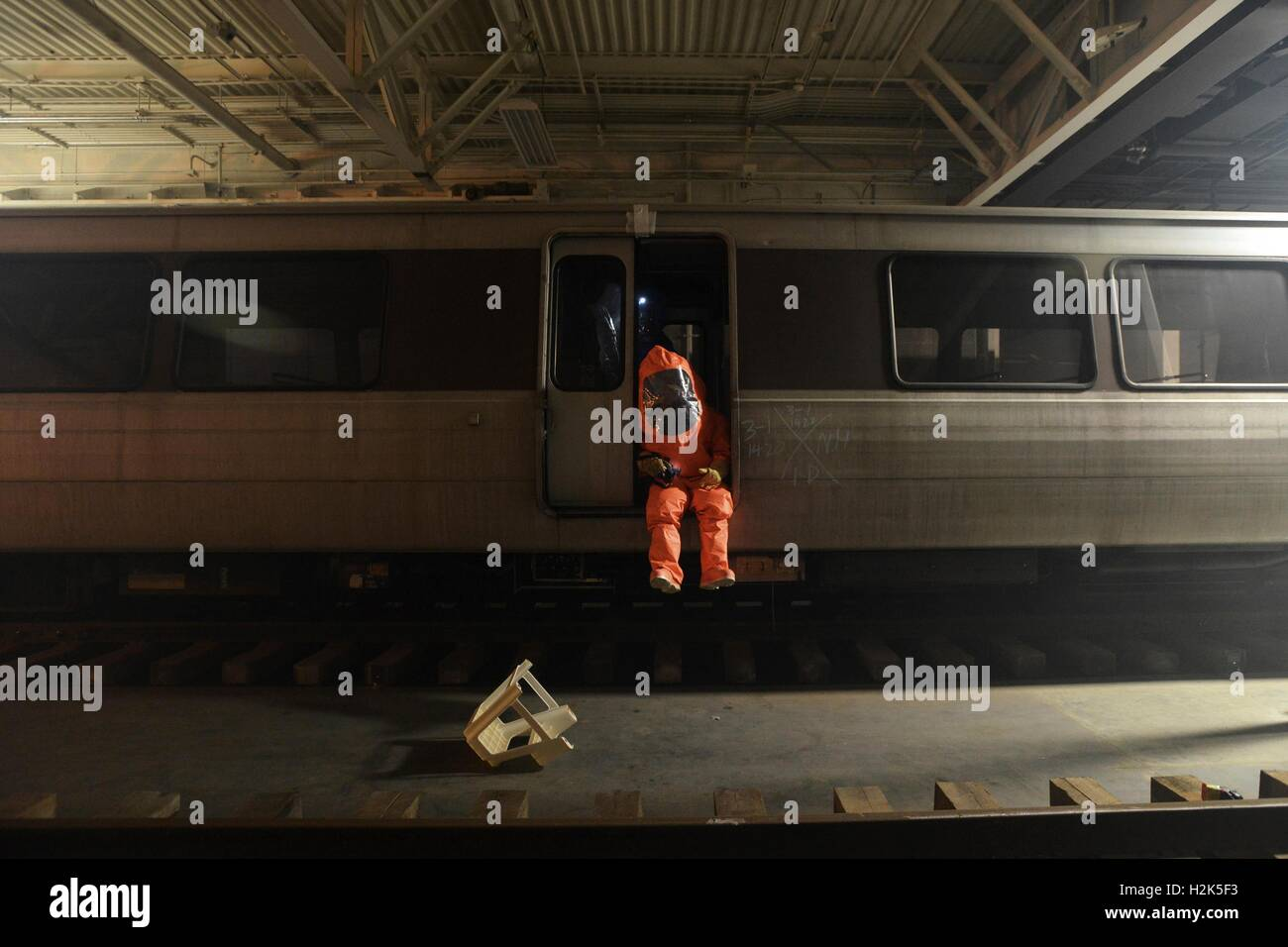 Soldiers wear protective clothing while checking a passenger train for radioactive contaminants during Global Dragon - Stock Image
