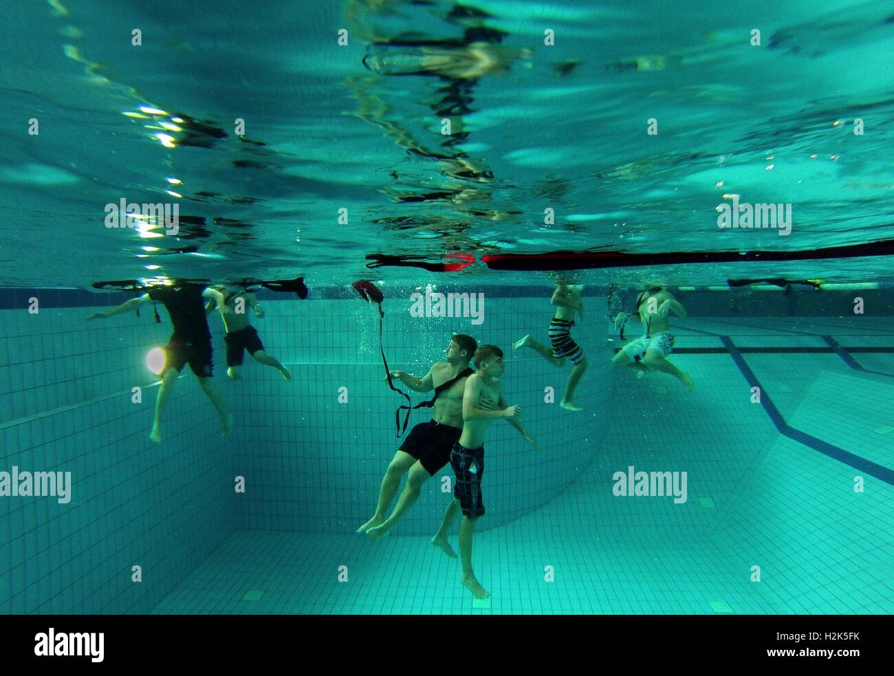 Participants practice rescuing a drowning victim in a pool during a lifeguard course simulation at the Ramstein - Stock Image