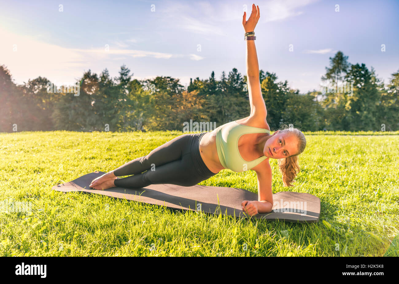 Young woman in sportswear doing side plank, workout on mat in park, Munich, Upper Bavaria, Bavaria, Germany - Stock Image