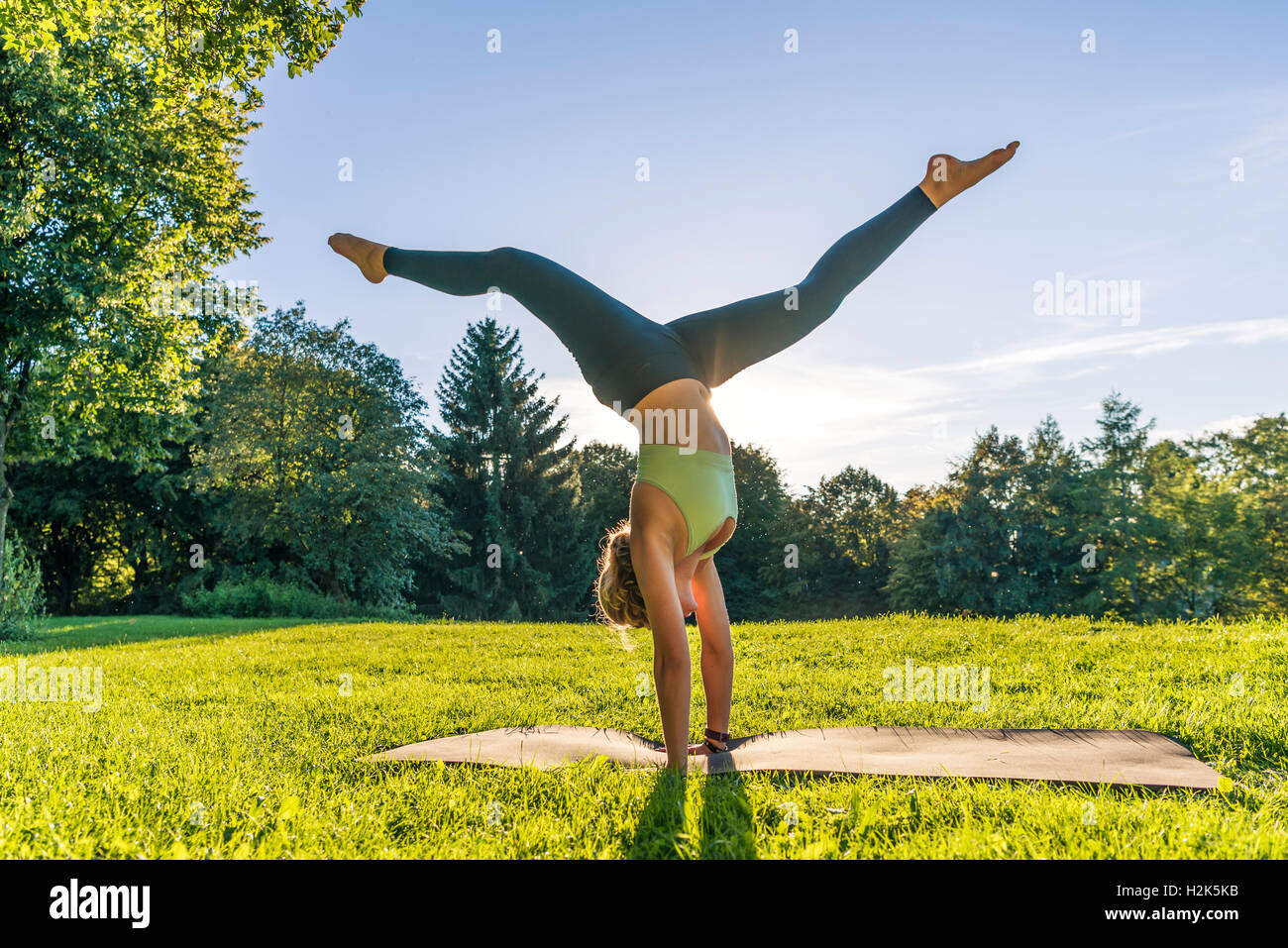 Handstand, young woman in sportswear doing workout on mat in park, Munich, Upper Bavaria, Bavaria, Germany - Stock Image