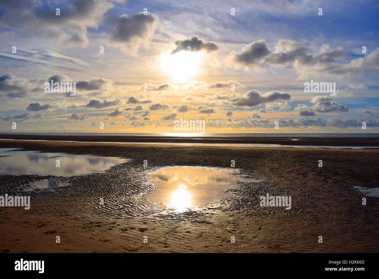 Sun in the sky over sandy beach with tide out - Stock Image