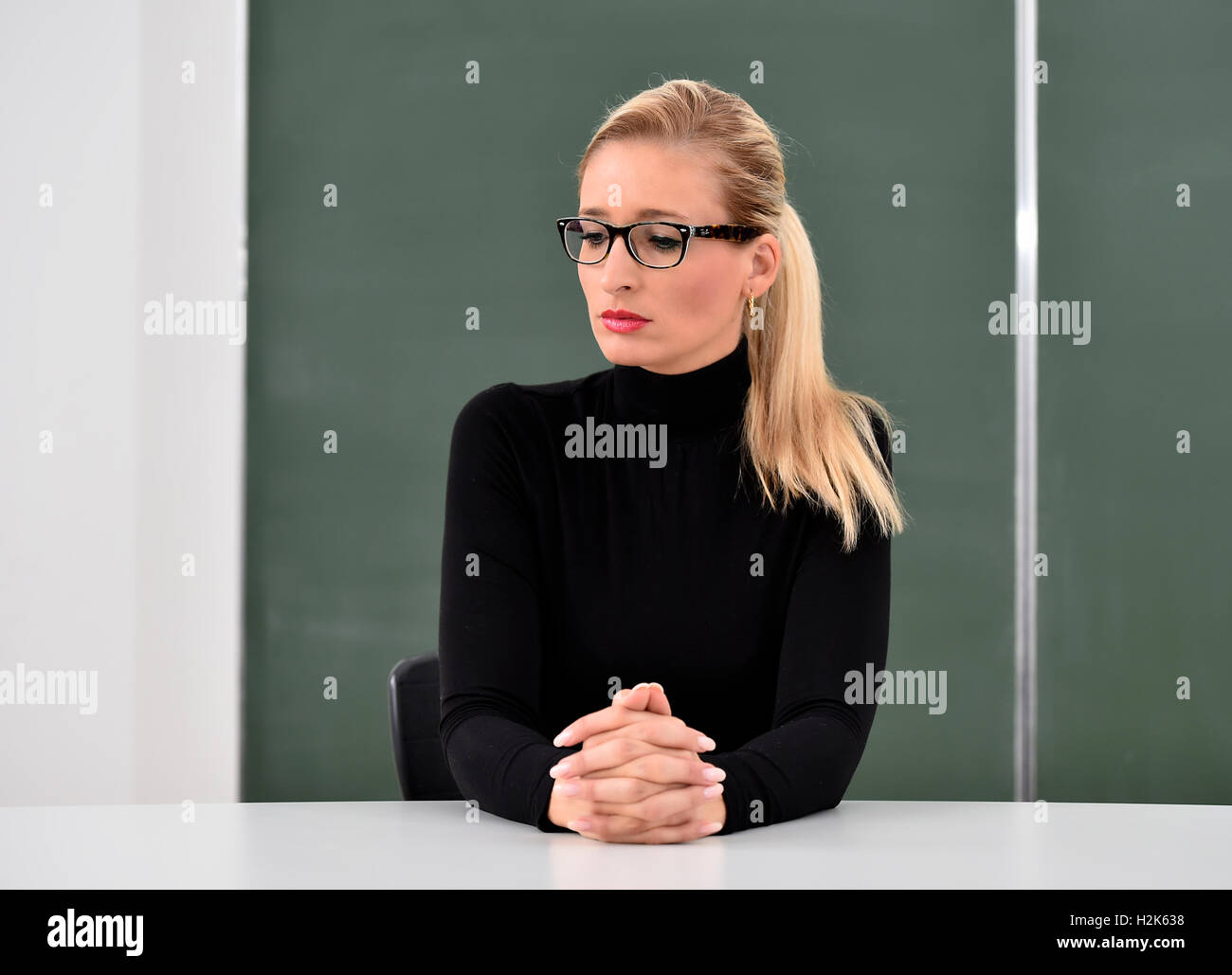Stressed, thoughtful teacher, tutor, trainer in front of a blackboard - Stock Image