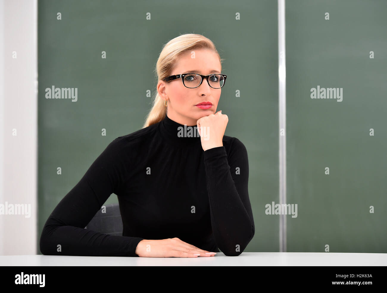 Stressed, thoughtful teacher, tutor, trainer, in front of a blackboard - Stock Image