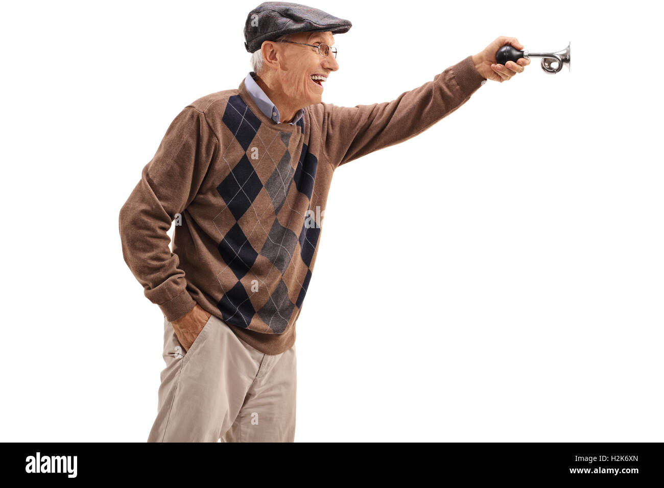 Excited elderly man honking a horn isolated on white background - Stock Image