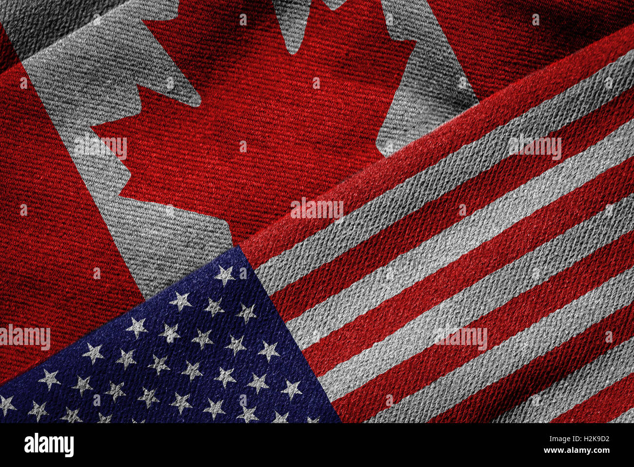 3D rendering of the flags of USA and Canada on woven fabric texture. Detailed textile pattern and grunge theme. Stock Photo