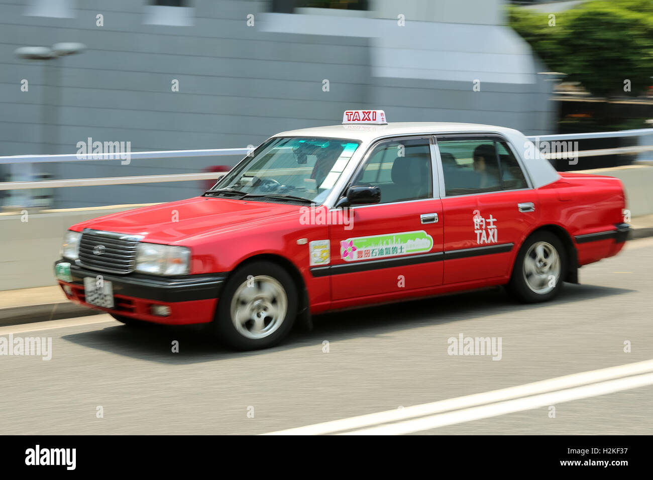 HONG KONG, - August 30, 2016: Red moving Hong Kong Taxi on a road with motion blur - Stock Image