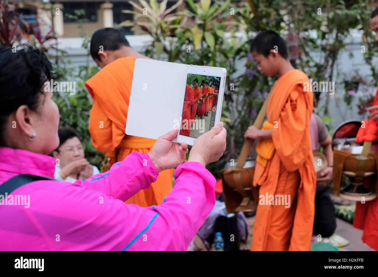 Tourist taking picture of Laos Monks on Tablet computer - Stock Image