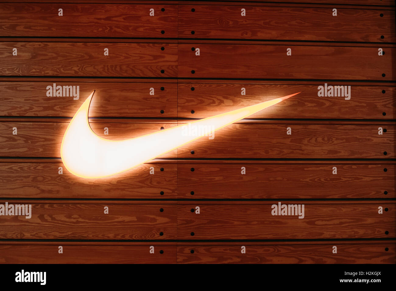 Vilnius, Lithuania - July 08, 2016: Close The Glowing Yellow Logotype Swoosh Of Nike Brand At Wooden Batten Wall - Stock Image