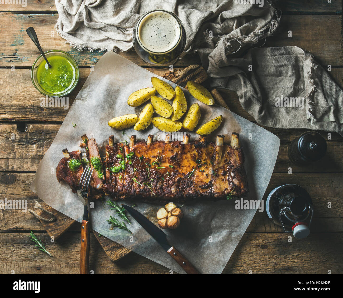 Roasted pork ribs partly cut into pieces with garlic, rosemary, green herb sauce, fried potato and dark beer on - Stock Image
