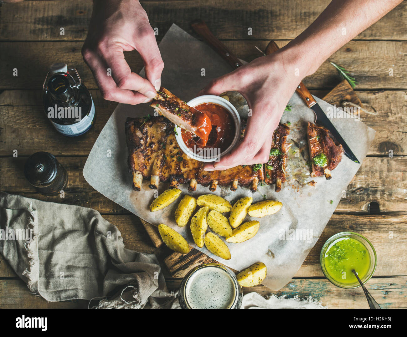 Man eating roasted pork ribs with potato pieces, garlic, rosemary and green herb sauce on rustic wooden table. Man' - Stock Image