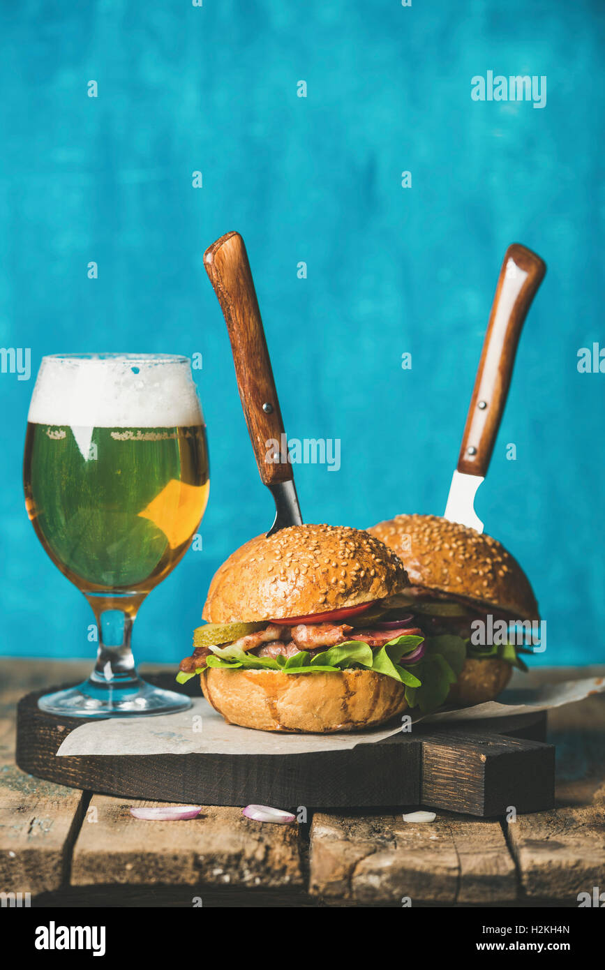 Homemade beef burgers with crispy bacon, onion, pickles, fresh vegetables, glass of wheat beer on serving wooden - Stock Image