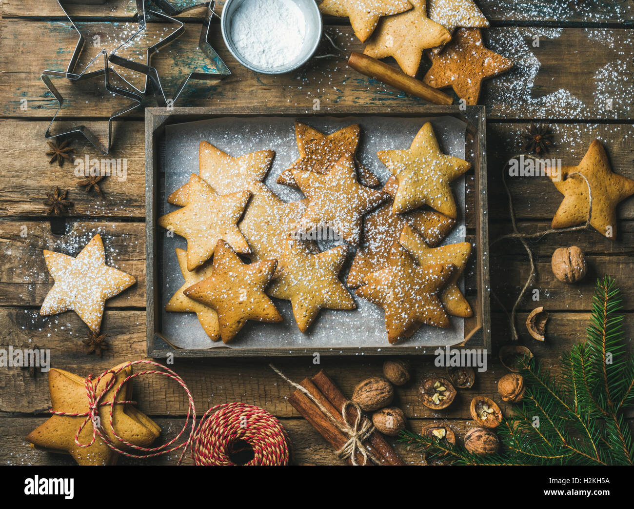 Gingerbread star shaped cookies in wooden tray with baking paper at bottom, sugar powder, nuts, spices, baking molds, - Stock Image