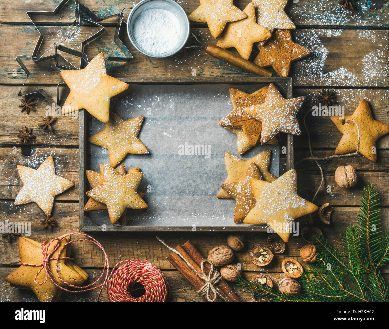 Christmas or New Year holiday background. Gingerbread cookies, sugar powder, nuts, spices, baking molds, fir-tree - Stock Image