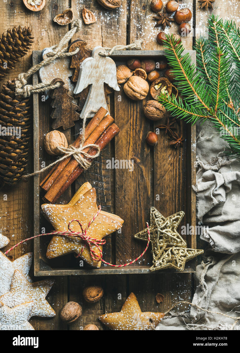 Gingerbread star shaped cookies, wooden angels, decorative stars, nuts and spices in wooden tray with sugar powder - Stock Image