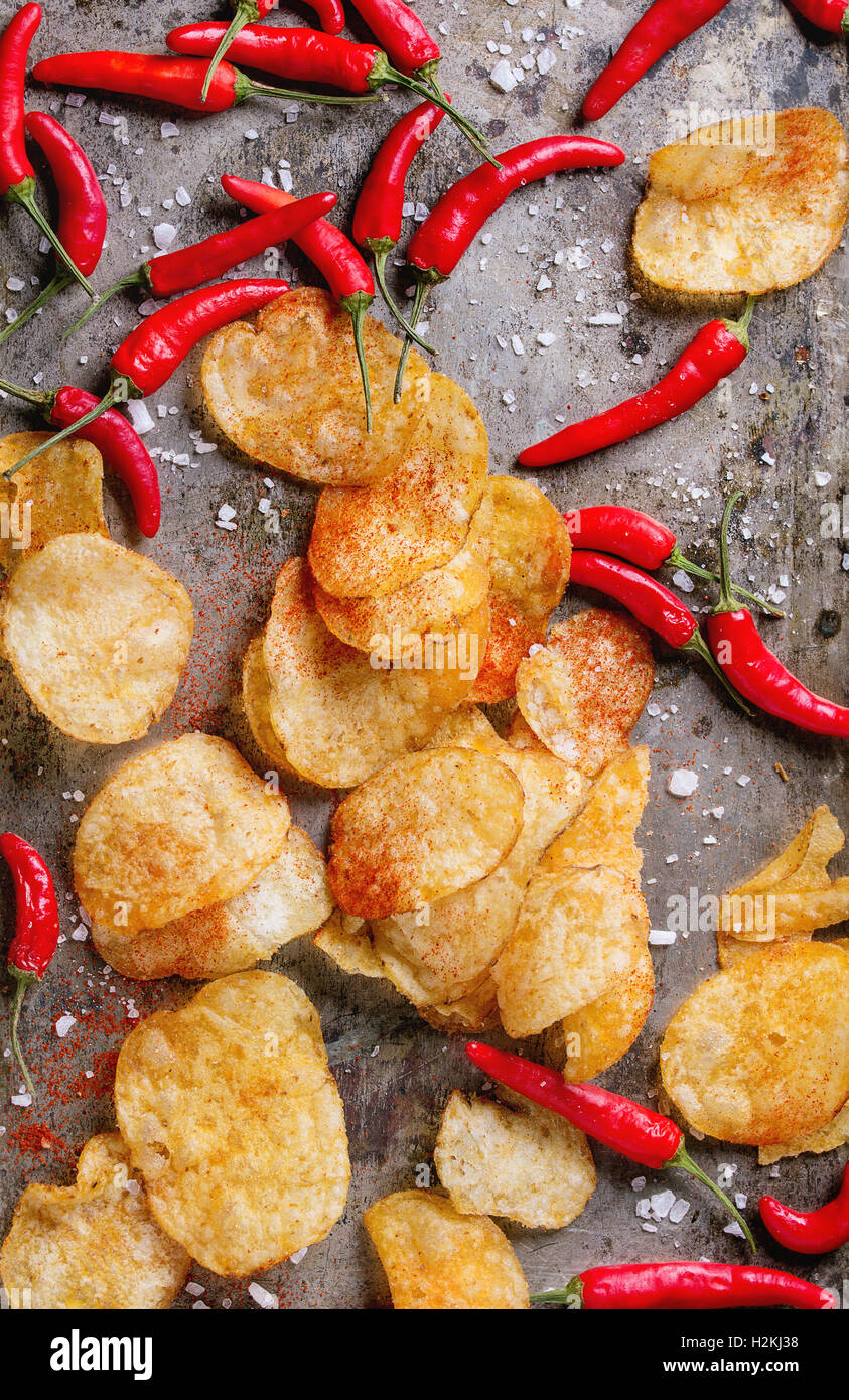 Heap of with spicy potato chips and tomato sauce with sea salt and red hot chili peppers fresh and powder over old - Stock Image
