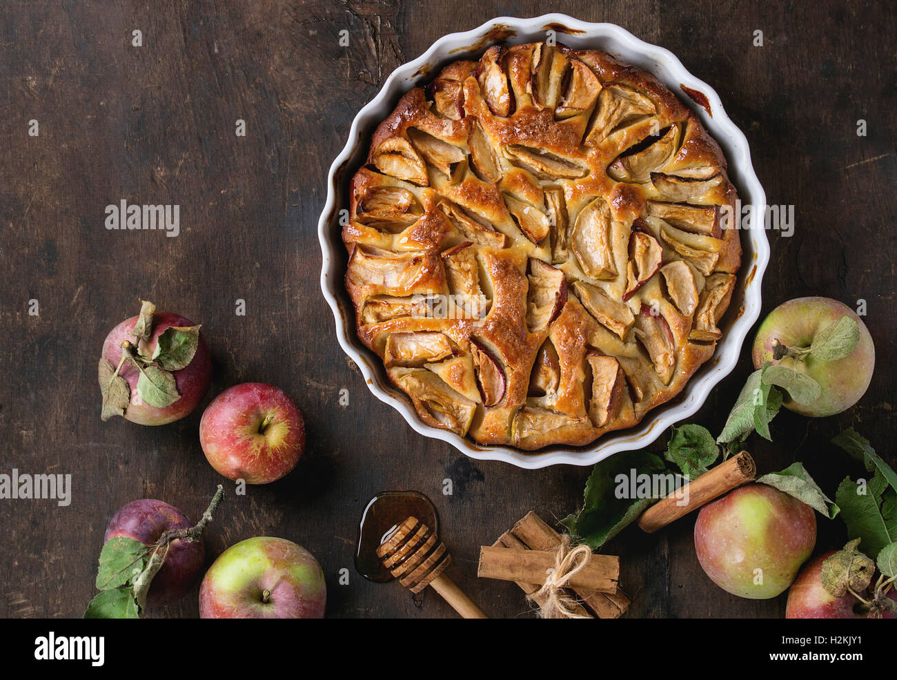 Homemade apple cake pie in white ceramic form with fresh apples with leaves, honey and cinnamon sticks over dark - Stock Image