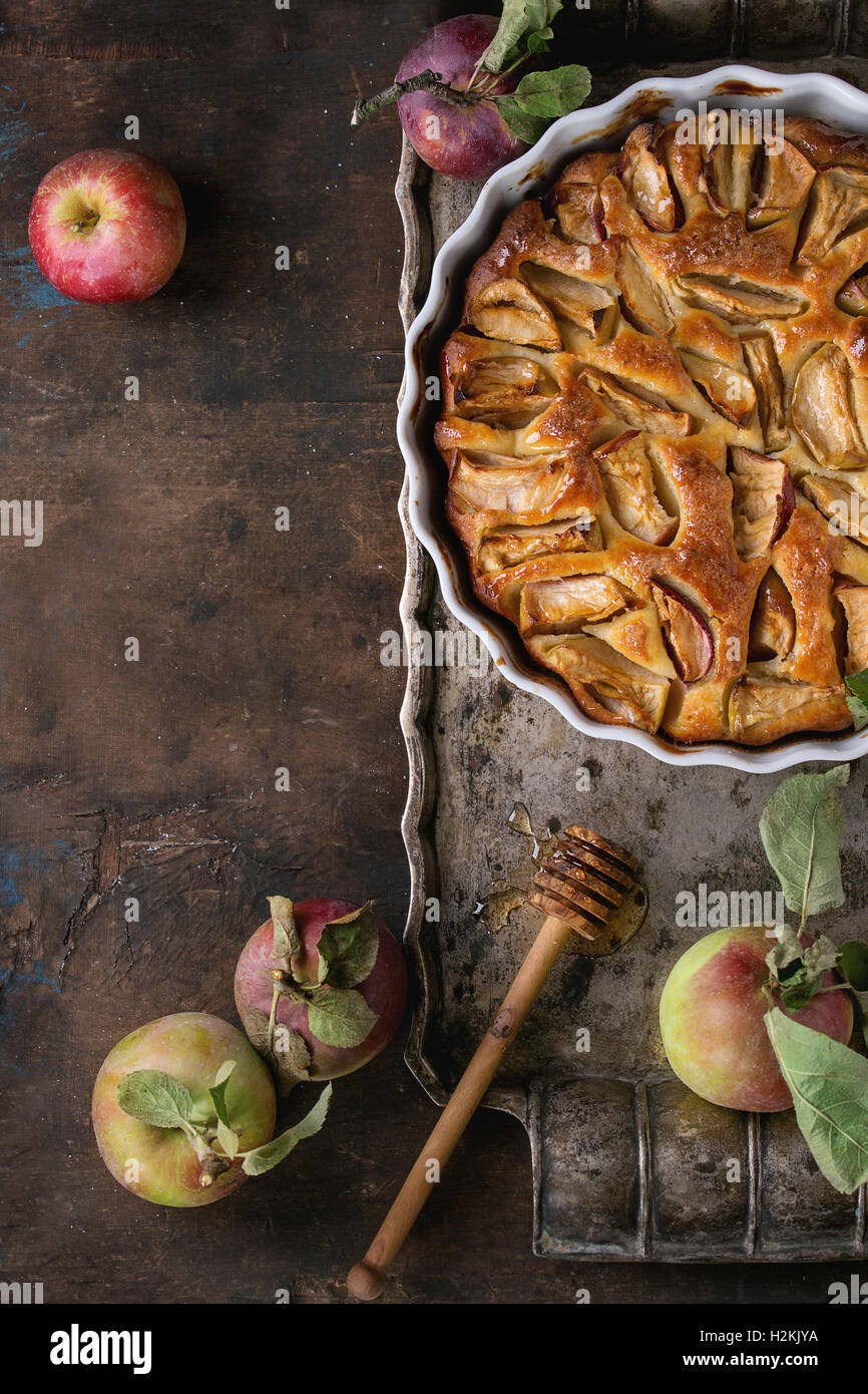 Homemade apple cake pie in white ceramic form on vintage metal tray with fresh apples with leaves and honey over - Stock Image