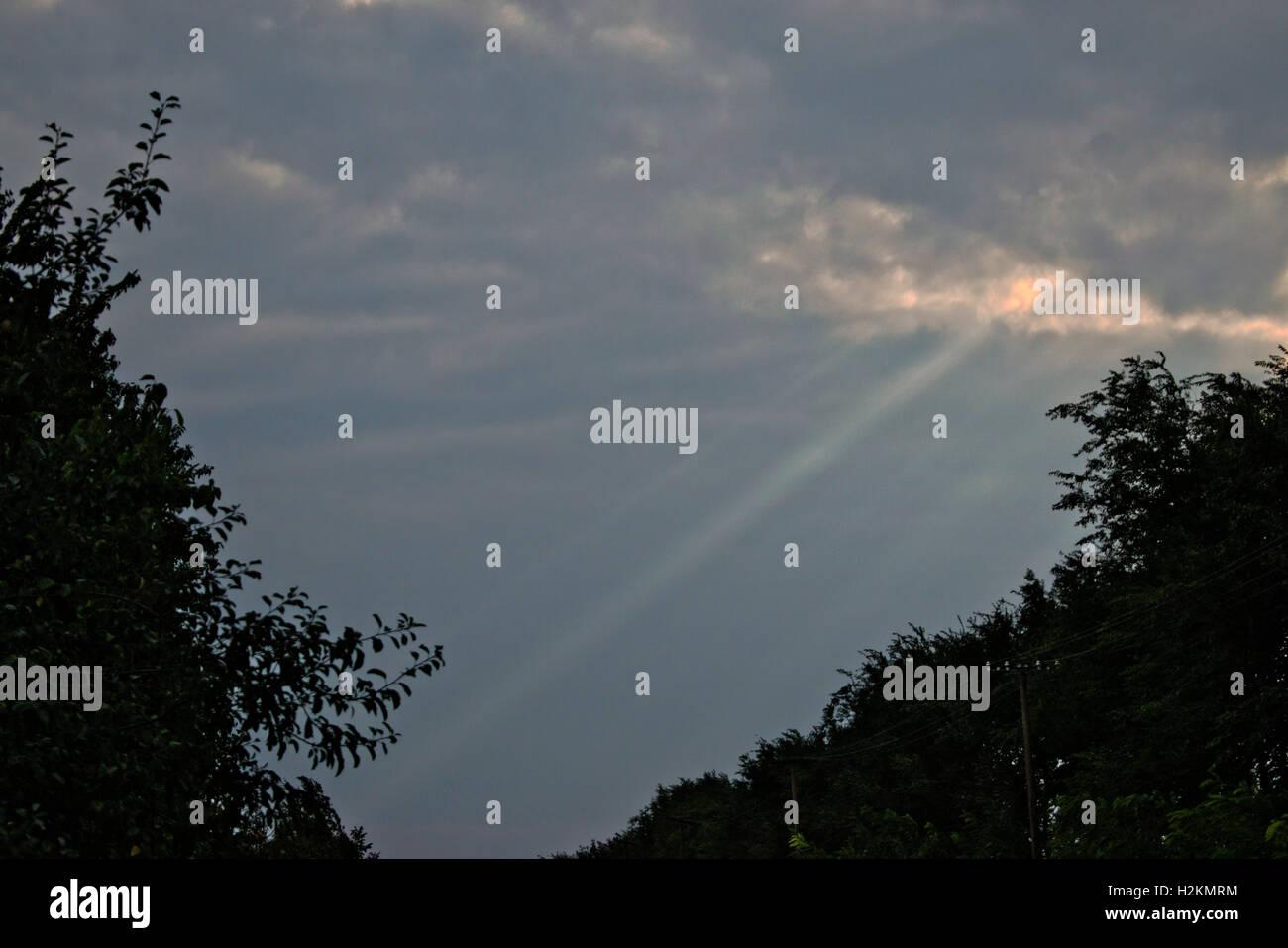 Bright rays of sun bursting through dark clouds - Stock Image