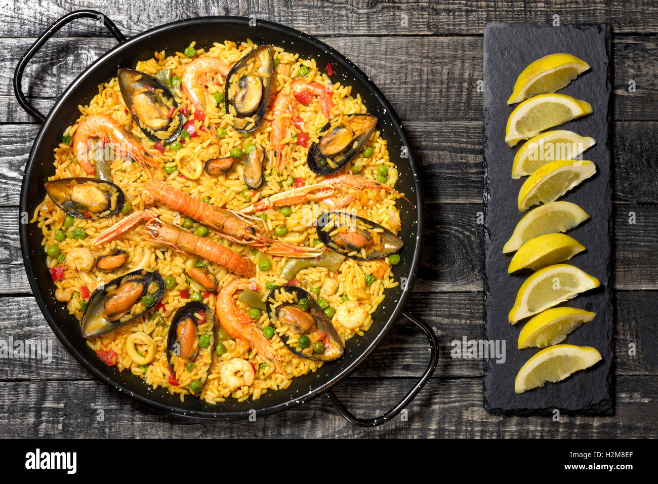 Spanish paella on a dark wooden table with lemon on a slate plate - Stock Image