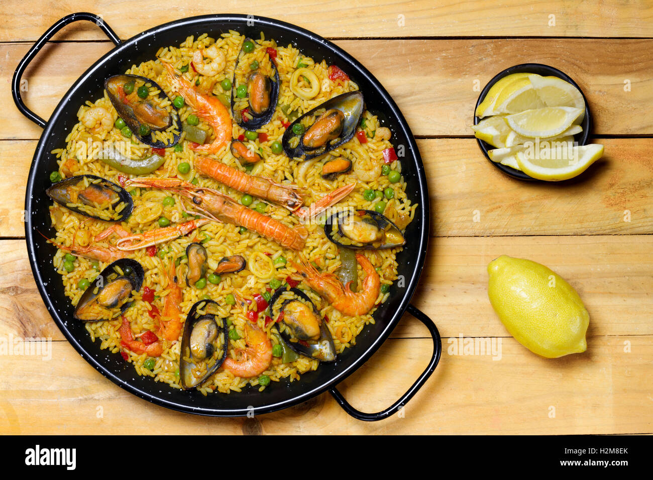 Spanish paella on a wooden table with lemon - Stock Image